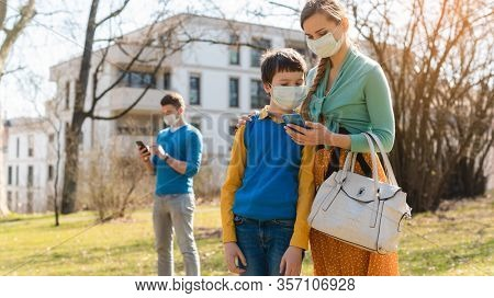 Family during corona crisis checking news on their phones standing in park