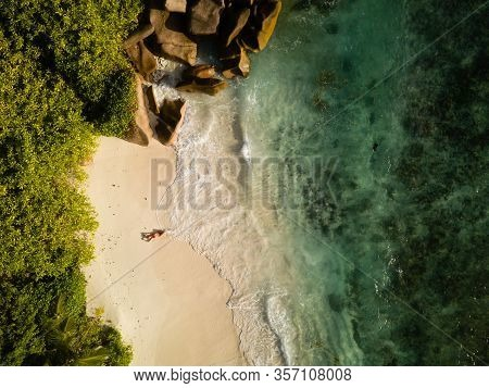 Tropical Beach, Coral Sand, Green Vegetation, Large Rocks, Waving Ocean, Splashes, And A Red Swisuit