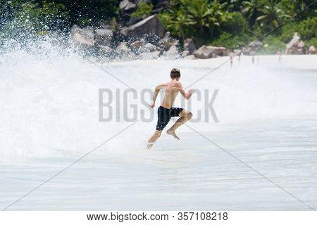Young, Teenager Slender Boy Runs Away From Splashing Wave At Beach Of Seychelles