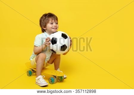 Amazed Little Boy Play With Soccer Ball While Sitting On Pennyboard Or Skateboard Over Yellow Backgr