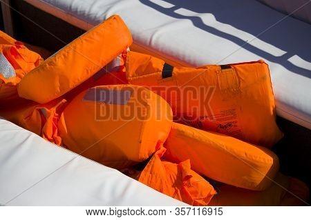 Orange Lifejackets For Tourists In A Pleasure Boat. Safety Precautions At Sea