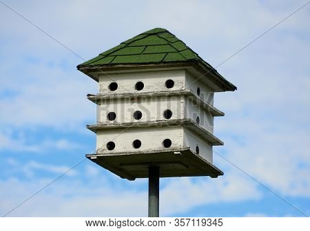 A Three Tier White Wooden Bird House With Green Roof