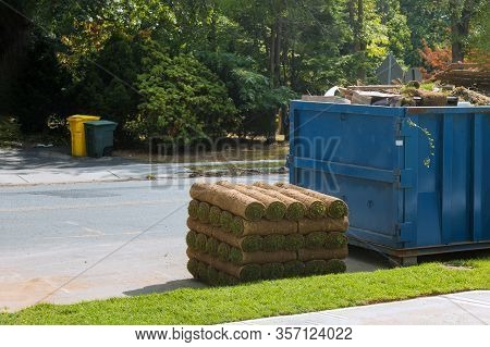 Installation Of A Modern Landscape Stacks Of Sod Rolls For New Lawn And Dumpster Full Garbage Contai