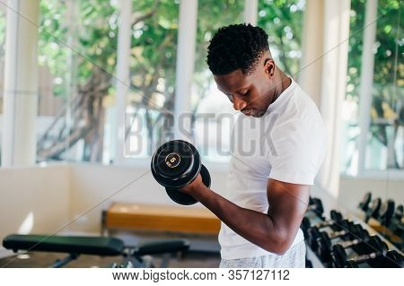 Young African American Man Standing And Lifting A Dumbbell With The Rack At Gym. Male Weight Trainin