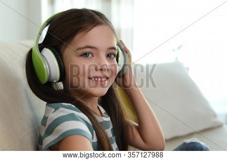 Cute Little Girl With Headphones Listening To Audiobook At Home