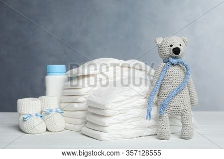 Baby Diapers, Booties, Bottle And Toy Bear On White Wooden Table Against Grey Background