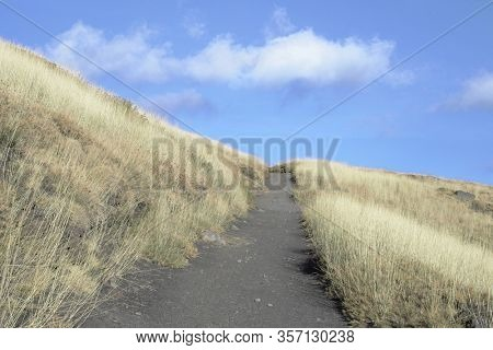 mountain path and white low clouds in Etna Park, Sicily