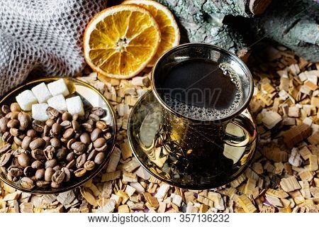Aromatic Dark Coffee With Bubbles On The Surface In A Dark Gold Cup On A Saucer, Next To Whole Grain