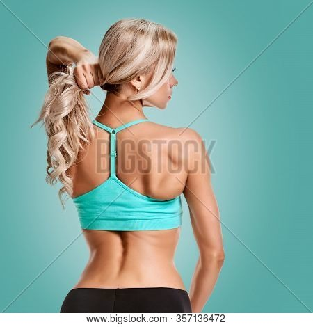 Back Of Beautiful Athletic Blonde Woman With Muscular Body On Green Jungle Background