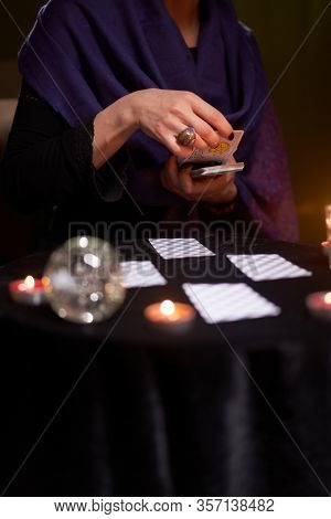 12.02.20. Moscow, Russia. Fortuneteller divines on cards at table with candles