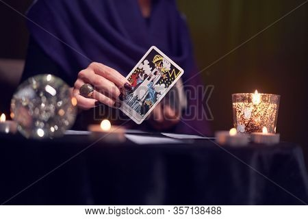12.02.20. Moscow, Russia. Fortuneteller female divines on cards at table with candles in dark room