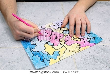 Man Draws An Abstract Imaginary Picture With A Pink Pencil And Decorates It With Different Colors, A