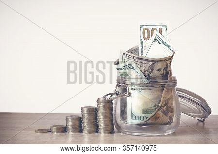 Coins Stack And Us Dollar Bills In The Glass Jar. Concept Of Money Saving, Financial. Savings Money