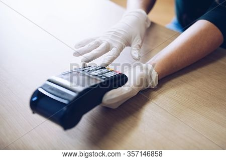 Woman Gives The Terminal For Non-contact Card Payment.she Wears Protective Gloves.