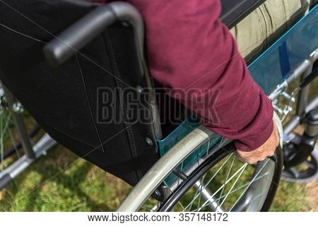 Hand Of A Paralyzed Adult Man In A Wheelchair