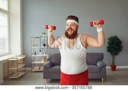 Funny Fat Man With Dumbbells Doing Exercises In The Room.