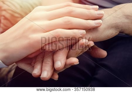 Hands Of A Young Girl Holding The Hands Of An Old, Elderly Woman Close Up. Concept Two Generations O