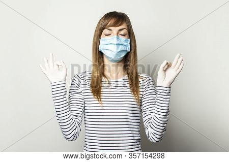 Young Woman In Protective Medical Mask And Latex Gloves Meditates On A Light Isolated Background. Co