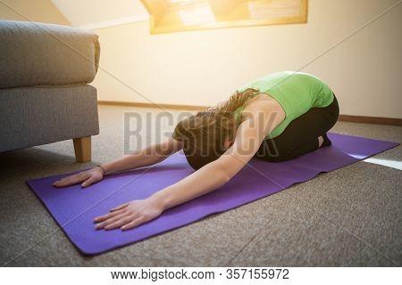 Young Woman Is Practicing Yoga At Home. Shashankasana / Hare Pose