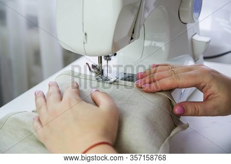 Modern Sewing Machine On A White Table. A Woman Sews From Linen Fabric On A Sewing Machine.