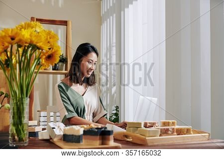 Smiling Young Asian Woman Making Website For Selling Handmade Soap Online