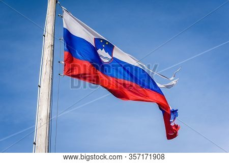 Torn And Worn Out Slovenian Flag Waving In The Wind. Damaged, Worn Out, Ripped Fabric Of Slovenia Fl