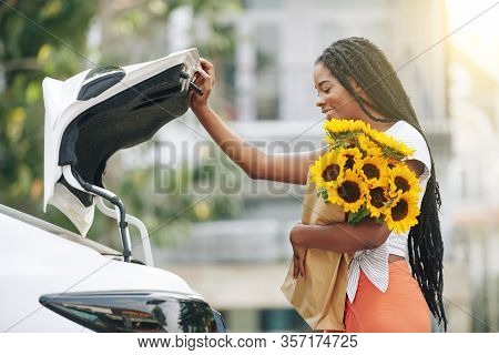 Smiling Pretty Young Black Woman Opening Truck Of Her Car To Put In Grocery Bag After Shopping