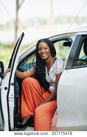 Pretty Young Smiling Black Woman With Dreadlocks Sitting In Her New Car