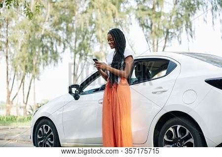 Cheerful Young Black Woman With Long Hair Standing Next To Her Car And Sending Text Messages To Frie