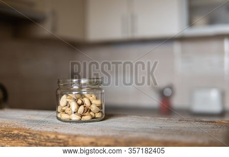 Pistachios In A Jar Which Standing On A White Vintage Table With A Kitchen On Background. Pistachio
