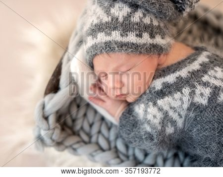 Cute newborn in knitted gray suit sleeping on stomach
