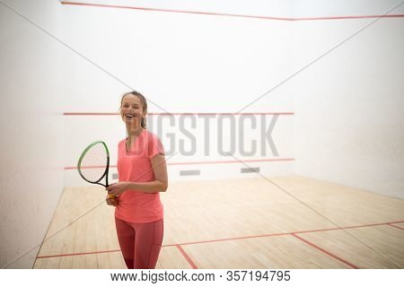 Pretty, female squash player on a squash court (motion blurred image; color toned image)