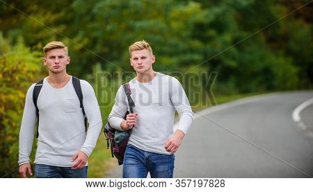 Company Friends Travelers Hitchhiking At Road Nature Background. Begin Great Adventure In Your Life