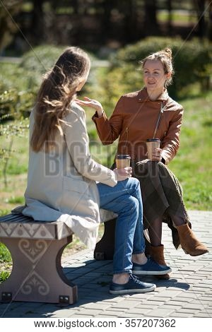 Two Attractive Girls Are Talking In The Park, Smiling And Laughing. Concept Of Takeaway Coffee, Natu