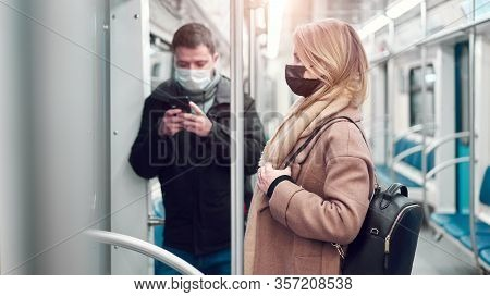 Brunet Man With Phone In Hands And Woman In Medical Masks Standing In Subway Car. Coronavirus Pandem