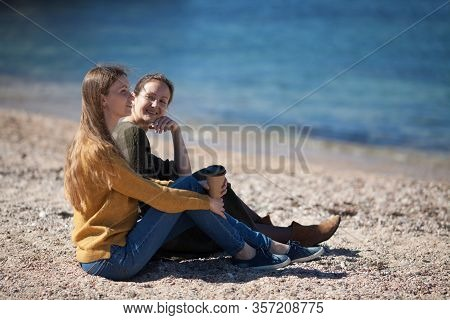Two Friends Of The Girl Communicate And Watch The Sea. Rear View. The Concept Of Live Communication,