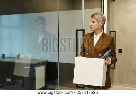Waist Up Portrait Of Mature Businesswoman Holding Box With Personal Belongings And Looking Away Whil