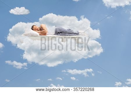 Man in pajamas sleeping on a mattress and floating in the sky surrounded by clouds