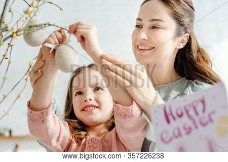 Selective Focus Of Smiling Mother And Daughter Looking At Decorative Easter Eggs