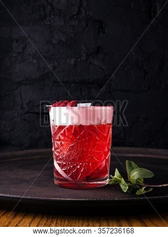Red, Sweet Berry Cocktail With Froth, Decorated With Raspberries On A Skewer In A Glass.