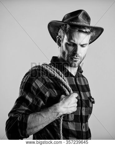 Western Life. Man Cowboy Beige Background. Man Wearing Hat Hold Rope. Ranch Occupations. Lasso Tool