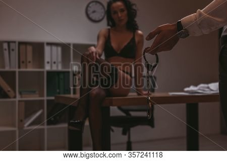 Cropped View Of Businessman Holding Handcuffs And Sexy Secretary Sitting On Desk In Lingerie