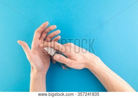 Hands Hold A Set Of Hygienic Antiseptics And Medications On A Blue Background. Antibacterial Protect