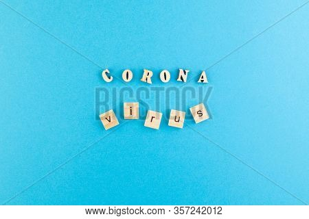 The Inscription Coronavirus Laid Out Of Wooden Cubes On A Blue Background. Medical Concept For Healt