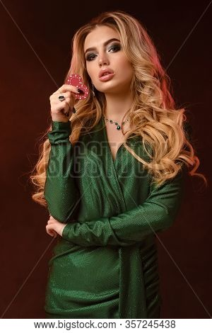Blonde Female, Bright Make-up, Green Stylish Dress And Jewelry. Showing Two Red Chips, Propping Her