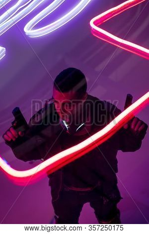 Overhead View Of Armed Bi-racial Cyberpunk Player Holding Guns Near Neon Lighting