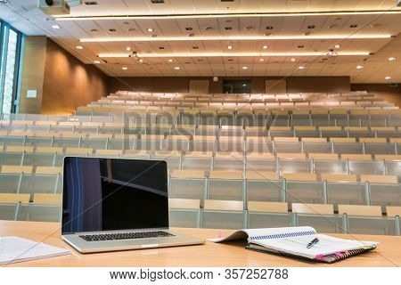 Photo of laptop on professor desk with lesson plan in empty classroom due to coronavirus