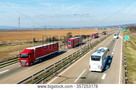 Convoy Of Red Transportation Trucks In Line Passing Two White Buses On A Rural Countryside Highway U