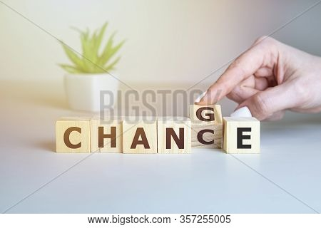 Businesswoman Hand Holding Wooden Cube With Flip Over Block Change To Chance Word On Table Backgroun