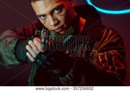 Selective Focus Of Armed Bi-racial Cyberpunk Player With Gun On Black